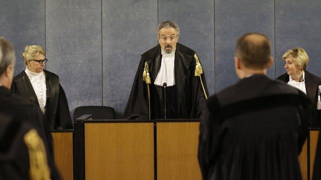 Court president Oscar Magi, centre, reads sentence