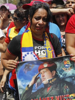 A woman weeps as she holds a picture of President Chavez