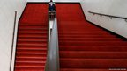 A security guard sits on the staircase next to a room for Tibetan Autonomous Region delegation