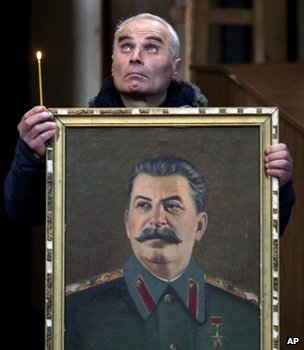 Georgian man holds a candle and a portrait of Joseph Stalin in a church in Gori