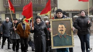 Georgians carry red flags and a portrait of former Soviet dictator Joseph Stalin during a ceremony marking the 60th anniversary of his death