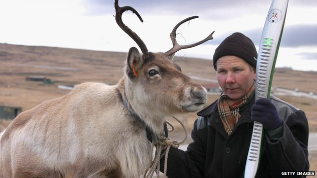 Mike Butcher with his reindeer 'Gordy' with the 2006 baton in the Falkland Islands