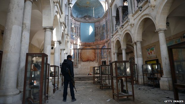 A Syrian rebel looks at damaged display cases inside a former church turned into a film museum which was shelled by government forces in Aleppo's old city on January 17, 2013.