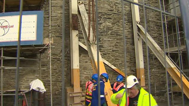 Workmen remove the support post