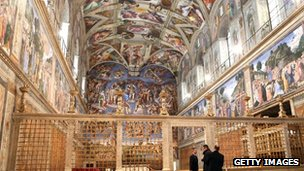 Clergy and workers make arrangements in the Sistine Chapel before the papal conclave