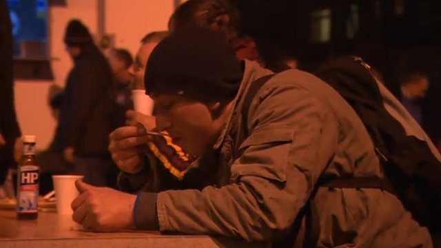 People eating hot food served by the soup kitchen