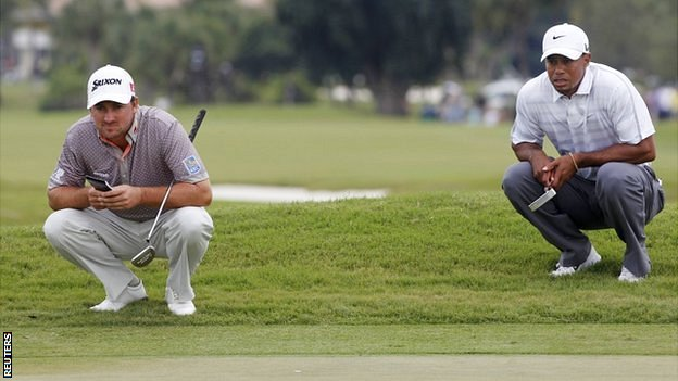 Graeme McDowell and Tiger Woods assess the green in Miami