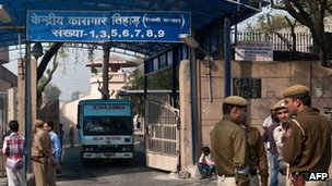 Indian policemen stand guard as an ambulance leaves the main entrance of Tihar Jail in New Delhi on March 11, 2013.