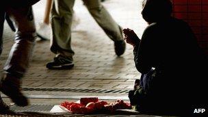 An elderly man begging on a street in Hong Kong