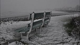 Bench in snow along Guernsey's east coast