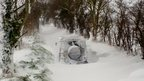 A land rover stuck in thick snow on a country lane.