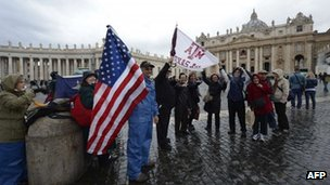"""Faithfuls from USA wave a flag as they arrive at St Peter""""s square on the first day of the conclave"""