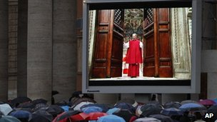 """People watch on a video monitor in St. Peter""""s Square as Monsignor Guido Marini, master of liturgical ceremonies, closes the double doors to the Sistine Chapel"""