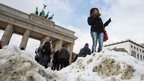 A tourist stands in front of the Brandenburg Gate in Berlin, Germany (12 March 2013)