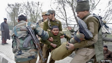 Indian paramilitary soldiers carry an injured colleague to a hospital during a fight in Srinagar on March 13, 2013