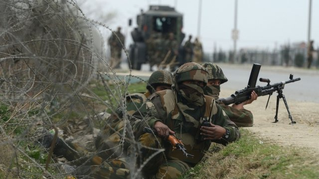 Indian soldiers take positions outside a school after an attack against Indian paramilitary personnel in Srinagar .
