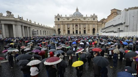 Crowds with umbrellas in St Peter's Square
