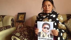 Purnimaya Lama holds up a picture of her dead husband Arjun