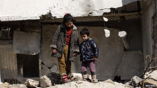 Children in Syria next to war torn buildings