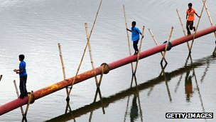 Children using a pipe as a bridge in Bangladesh
