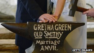 A bride and groom's hands on the anvil at the old smithy at Gretna Green