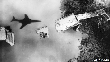 A US jet flies over a destroyed bridge in North Vietnam