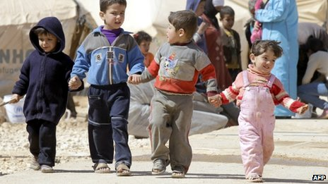 Syrian children walk amid tents at the Zaatari refugee camp, near the Syrian border with Jordan in Mafraq on 7 March 2013