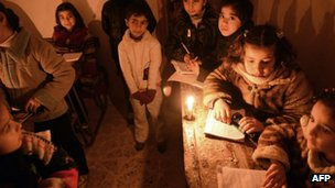 Syrian children attend an early morning class by candle light due to the lack of electricity at a school in Kadi Askar area in the northern city of Aleppo on 9 February 2013