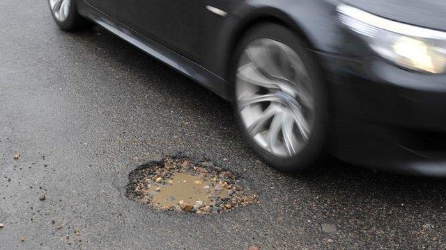 A car passing a pothole