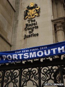 A Portsmouth FC scarf on railings outside the Royal Courts of Justice