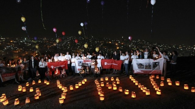 """Syrian and local children form the word """"Syria"""" with candles during a moment of silence the night before the second anniversary of the start of the Syrian Revolution at the Citadel"""