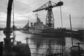 HMS Belfast moored at Rosyth, adjacent to a large crane during World War II
