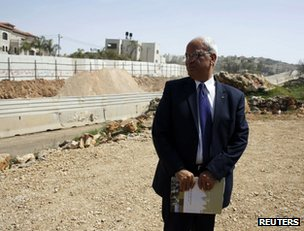 Palestinian chief negotiator Saeb Erekat stands near a road under construction on disputed land in Jerusalem, 14 March