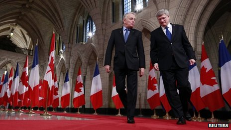 France's Prime Minister Jean-Marc Ayrault (L) and Canada's Prime Minister Stephen Harper walk down the Hall of Honour on Parliament Hill in Ottawa 14 March 2013