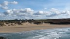 A sandy beach with green fields and sand dunes behind. Blue sky and fluffy clouds above.