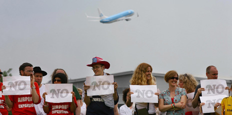 """Protesters hold up """"NO"""" signs outside Heathrow"""