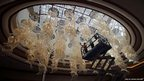 Workers put finishing touches on a huge chandelier at Solaire casino-resort in Pasay city, Metro Manila