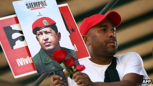 Supporter of Hugo Chavez watches procession. 15 March 2013