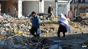 Residents walk through debris after a bombing in Quetta, Pakistan. Photo: February 2013