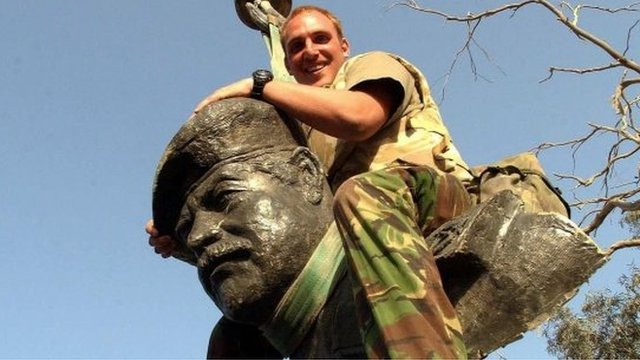 Member of armed forces on toppled Saddam Hussein statue