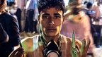 Faris Ali Mohammed al-Qadeemi holds up shell casings after soldiers fired on unarmed protesters