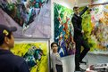 An exhibitor shows a painting at the Affordable Art Fair in Hong Kong