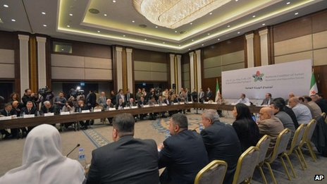 Head of the new Syrian National Coalition for Opposition and Revolutionary Forces Mouaz al-Khatib, rear-center, speaks during a meeting in Istanbul