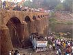 Rescuers and bystanders look at the wreckage of a passenger bus after it fell from a bridge in Ratnagiri district in India.