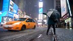 A woman tries, unsuccessfully, to hail a taxi cab during a snowstorm in Times Square in New York