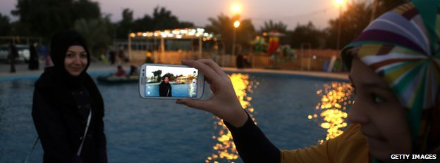 Iraqi woman uses her mobile phone to take a picture of her friend at an amusement park in Baghdad's Abu Nuwas street
