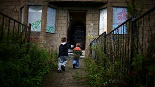 Children playing outside a derelict house