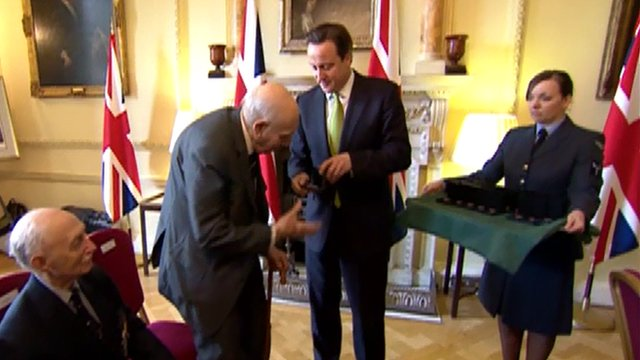 Prime Minister David Cameron presenting a veteran with an honour