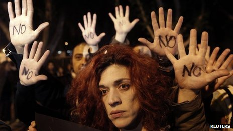 "Anti-bailout protesters raise their open palms showing the word ""No"" after Cyprus""s parliament rejected a proposed levy on bank deposits"