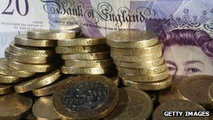 Pound coins stacked in front of a £20 note